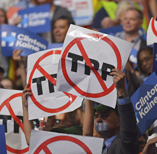 People hold signs against the Trans Pacific Partnership (TPP) on Day 3 of the Democratic National Convention at the Wells Fargo Center, July 27, 2016 in Philadelphia, Pennsylvania