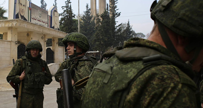 Russian soldiers stand next to an aid convoy in Aleppo, Syria, Sunday, Dec. 4, 2016