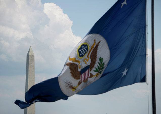 The Washington Monument is seen beyond the US State Department's flag June 30, 2015 in Washington, DC