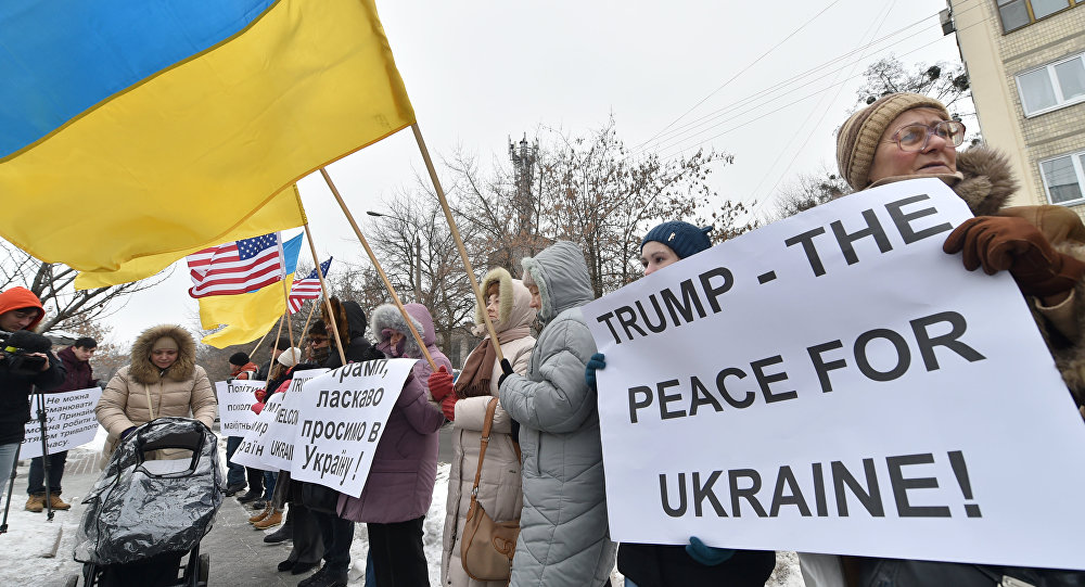 People hold Ukrainian and US flags and placards reading Trump welcome to Ukraine!, Trump - the peace for Ukraine! and the others during their rally in front of United States embassy in Kiev on January 20, 2017