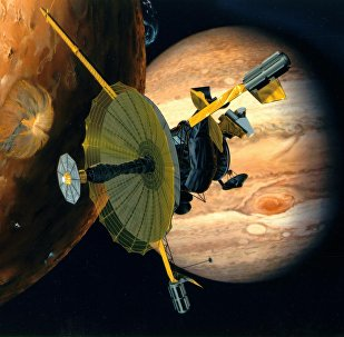 This NASA artist's concept shows the Galileo spacecraft flying by Jupiter's volcanic moon Io (L) and the gigantic planet (R).