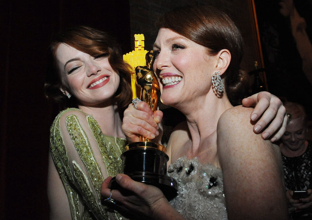 Nominee for Best Supporting Actress Emma Stone (L) embraces Winner for Best Actress Julianne Moore at the Governor's Ball following the 87th Oscars February 22, 2015 in Hollywood, California