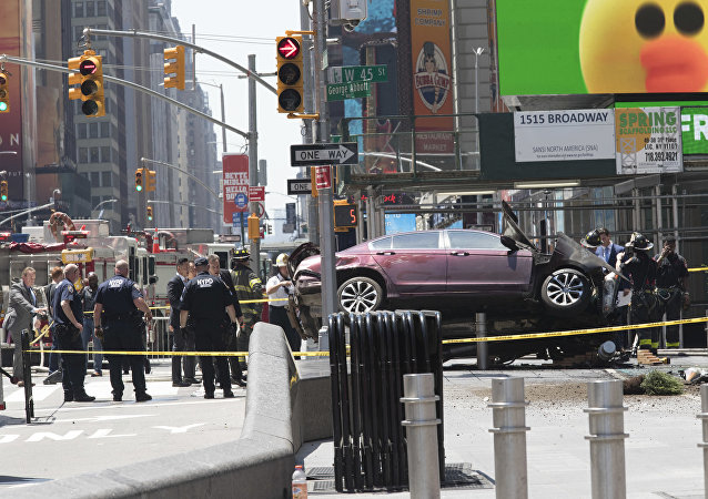 A car rests on a security barrier in New York's Times Square after driving through a crowd of pedestrians, injuring at least a dozen people, Thursday, May 18, 2017.