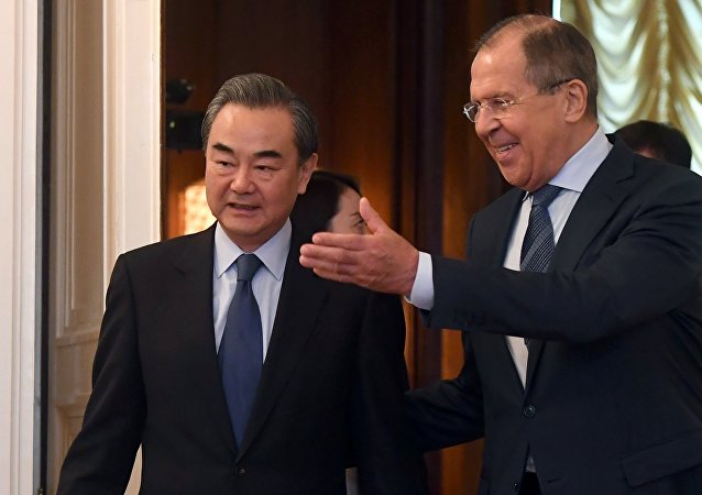 Russian Foreign Minister Sergei Lavrov (R) and his Chinese counterpart Wang Yi enter a hall during a meeting in Moscow