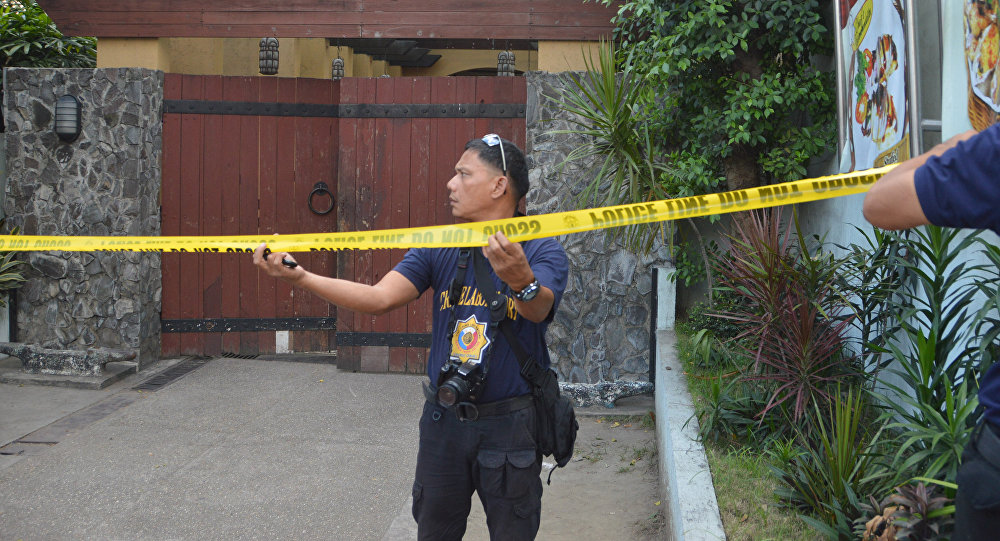 Police mark the crime scene with a yellow tape where two Chinese diplomats were killed in Cebu province, central Philippines on Wednesday Oct. 21, 2015