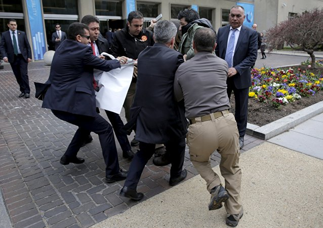 Turkish security personnel struggle to take a sign away from protesters in front of the Brookings Institute before the arrival of Turkish President Recep Tayyip Erdogan in Washington.