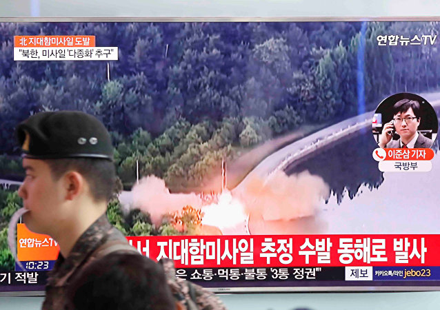 A South Korean soldier walks past a TV broadcast of a news report on North Korea firing what appeared to be several land-to-ship missiles off its east coast, at a railway station in Seoul, South Korea, June 8, 2017.
