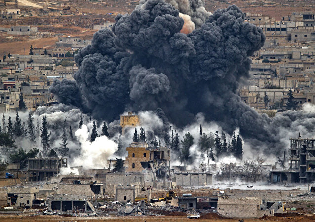 n this Nov. 17, 2014 file photo, smoke rises from the Syrian city of Kobani, following an airstrike by the U.S.-led coalition, seen from a hilltop outside Suruc, on the Turkey-Syria border.