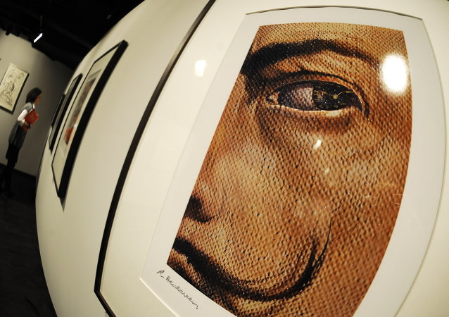 A woman walks past works by Spanish artist Salvador Dali as in the foreground can be seen a photocollage titled Macrophotographic Self-Portrait with the Appearance of Gala as a Spanish Nun at Berlin's new Dali Museum on February 3, 2009
