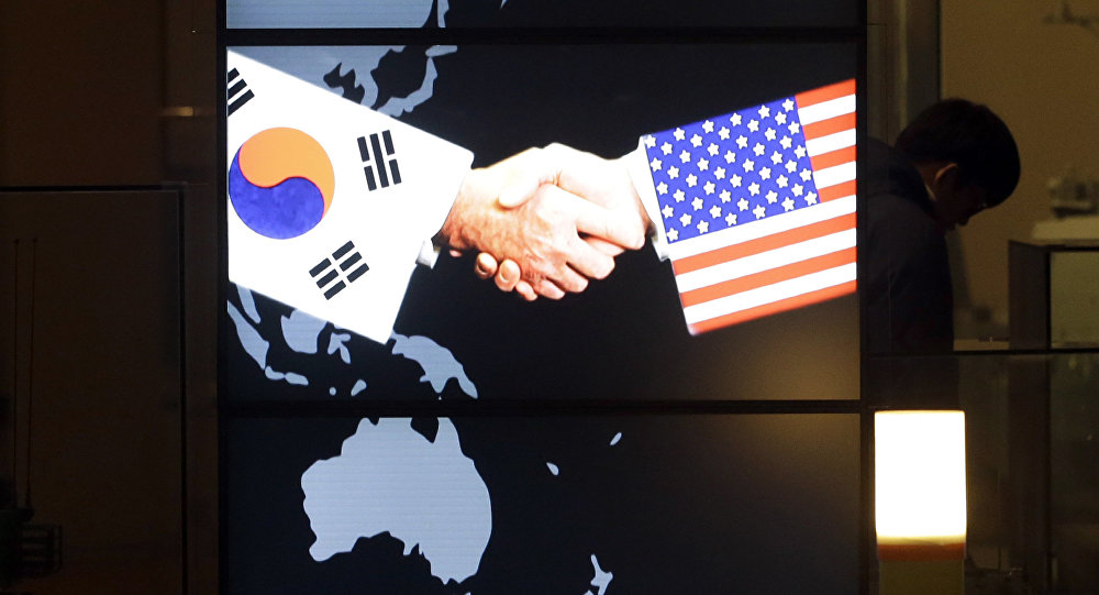 A visitor tour near the screen showing an image of a handshake by the U.S. and South Korean flags at the two countries' security alliance exhibition hall at the Korea War Memorial Museum in Seoul, South Korea, Wednesday, Jan. 14, 2015