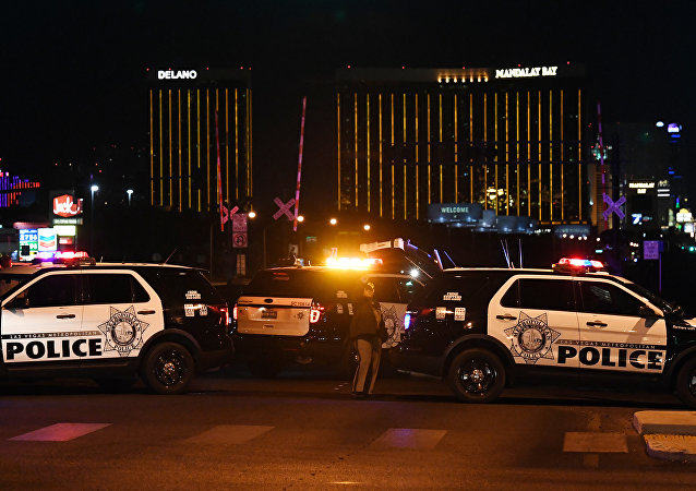Police form a perimeter around the road leading to the Mandalay Hotel (background) after a gunman killed at least 50 people and wounded more than 200 others when he opened fire on a country music concert in Las Vegas, Nevada